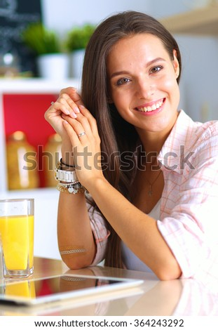 Woman using a tablet computer while drinking juice in her kitchen - stock photo
