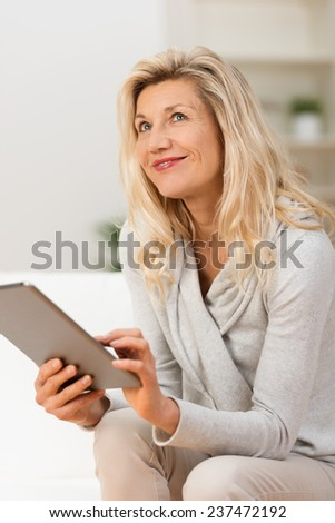 Woman using a tablet sitting thinking looking pensively up into the air with her finger poised over the touch screen - stock photo
