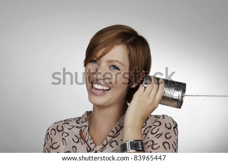 woman using a tin can to communicate - stock photo