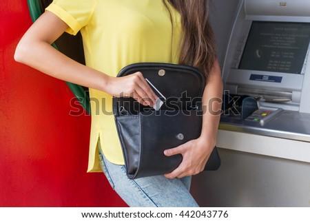 Woman using ATM machine card - stock photo