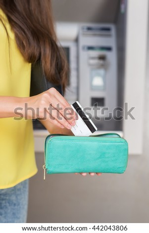 woman using ATM machine, card in wallet - stock photo