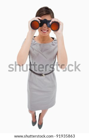 Woman using binoculars against a white background - stock photo