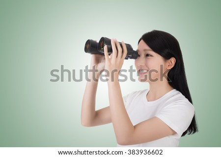 woman using binoculars, studio shot portrait