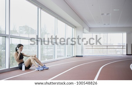 Woman using cell phone on side of indoor track - stock photo