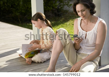 Woman using cell phone with daughter reading book on porch - stock photo
