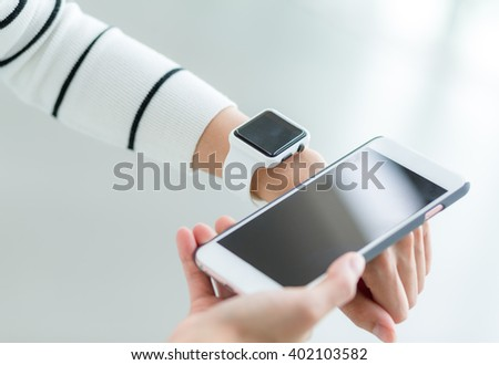 Woman using cellphone to connect with smart watch - stock photo
