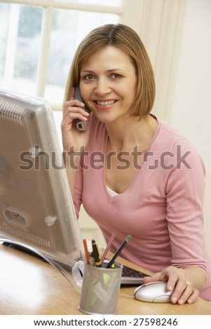 Woman Using Computer And Talking On Phone - stock photo