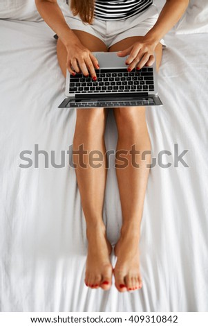 Woman Using Computer At Home. Closeup View Of Female With Long Fit Legs Typing On Laptop Keyboard While Relaxing On Bed. Girl Working Online On Notebook. Communication Technology.  - stock photo