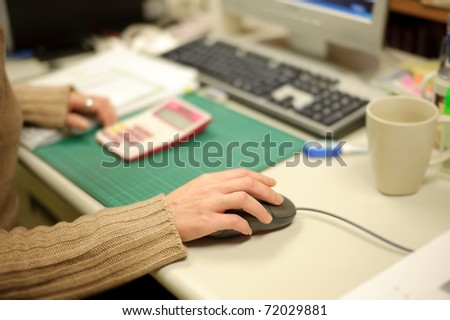 Woman using computer mouse, focus on hand.