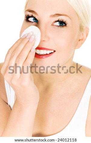 Woman using cotton pad on face - stock photo