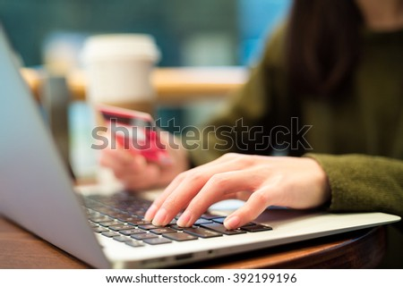 Woman using credit card for ordering ticket by laptop computer - stock photo