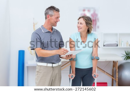 Woman using crutch and talking with her doctor in medical office - stock photo