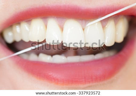Woman using dental floss - stock photo