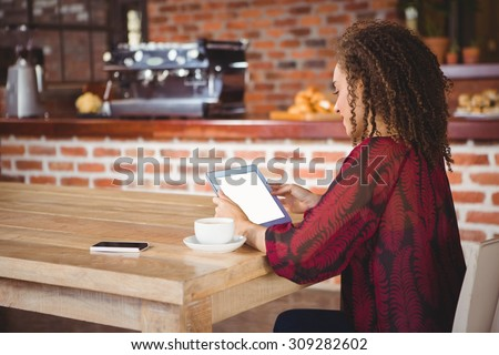Woman using digital tablet in a cafe - stock photo