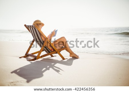 Woman using digital tablet on the beach on a sunny day - stock photo