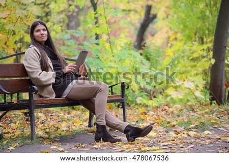 Woman using digital tablet sitting in autumn park