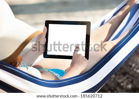Woman using digital tablet while relaxing in hammock at beach - stock photo