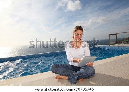 Woman using electronic tablet by swimming pool - stock photo