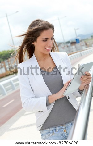Woman using electronic tablet in the street