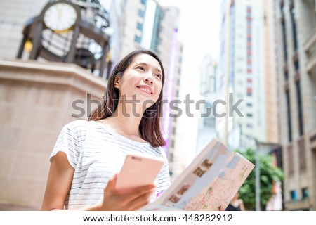 Woman using gps and city map to find the location in Hong Kong - stock photo
