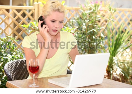 Woman using her laptop outside a cafe - stock photo