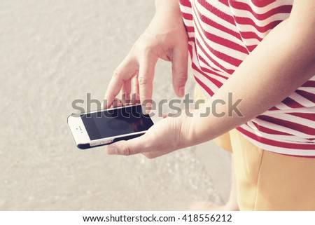 Woman using her Mobile Phone.on the beach.