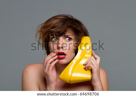 Woman using her shoe as phone