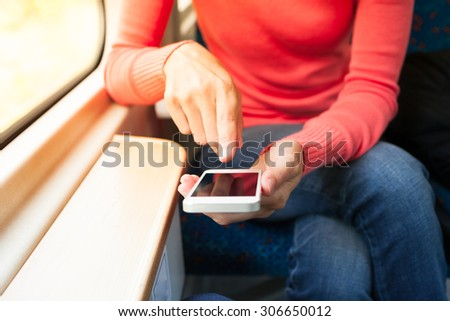 Woman using her smartphone of a train.  - stock photo