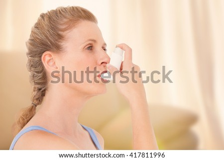 Woman using inhaler for asthma against light shining into living room - stock photo