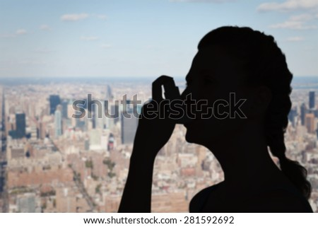 Woman using inhaler for asthma against new york - stock photo