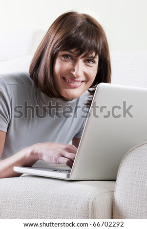 Woman using laptop at home - stock photo