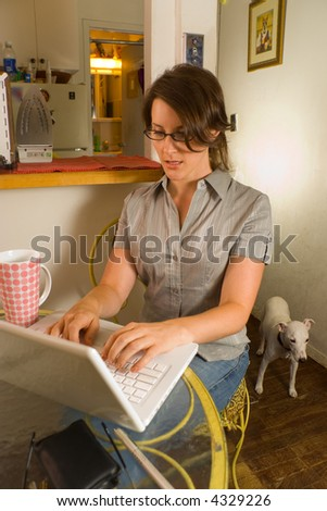Woman using laptop computer at home with pet dog - stock photo