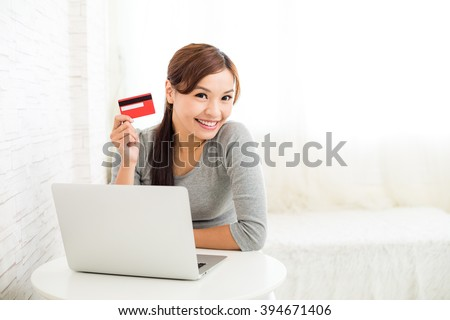Woman using laptop computer for online shopping - stock photo