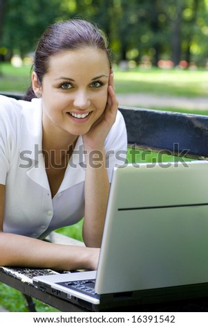 Woman using laptop on bench outdoors - stock photo