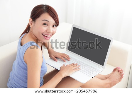 woman using laptop on sofa in the living room, empty computer screen is great for your copy space design, asian beauty - stock photo