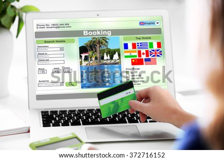 Woman using laptop to book hotel online - stock photo