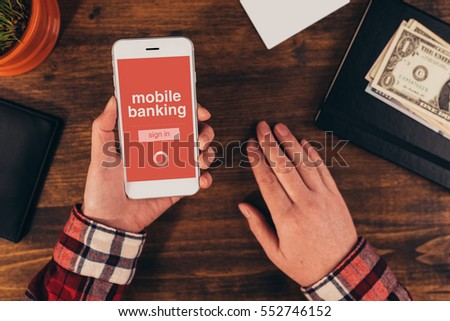 Woman using mobile banking app on smart phone in the office, top view