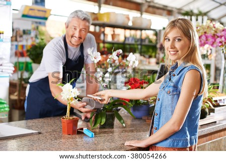 Woman using mobile payment with smartphone in a hardware store - stock photo
