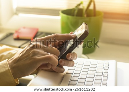 Woman using mobile phone, computer keyboard in the background. - stock photo