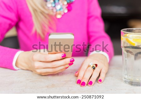 Woman using mobile phone in cafe - stock photo