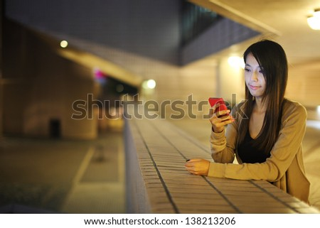 woman using mobile phone in city at night - stock photo
