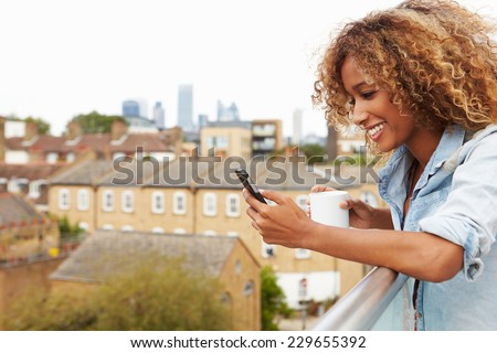 Woman Using Mobile Phone On Rooftop Garden Drinking Coffee - stock photo