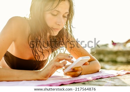 Woman using mobile phone on the beach - stock photo