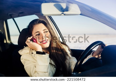 Woman using mobile phone while she is driving - stock photo