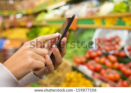 Woman using mobile phone while shopping in supermarket, vegetable department store - stock photo