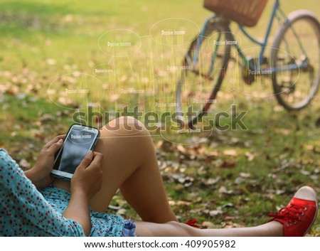 woman using mobile smart phone at the park and touch screen passive income