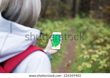 Woman using navigation app on smartphone - stock photo