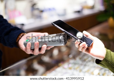 Woman using NFC technology to make payment - stock photo