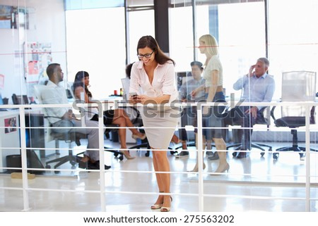 Woman using phone during office meeting - stock photo