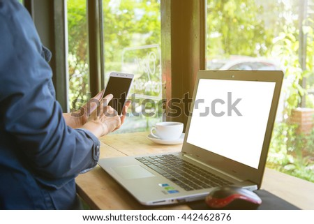Woman using smart phone and notebook with coffee on wooden table.Warm sunlight.